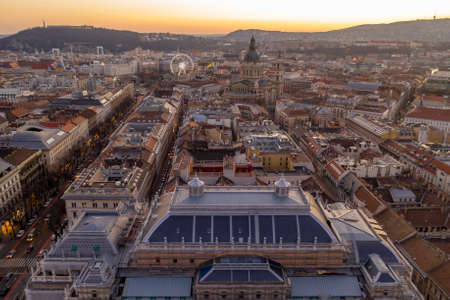 Aerial drone shot of St. Stephens Basilica over opera house in Budapest sunrise morning glow