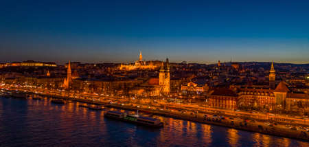 Aerial drone shot of St. Anne Parish church by Danube river at Budapest dusk city lights on