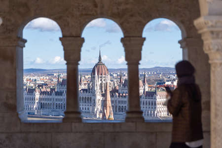 Hungarian Parliament view through corridor view on fishermans bastion with blurred tourists figure in Budapest