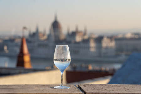 Reflection in wine glass of Hungary Paliament hazy figure in the background Stockfoto