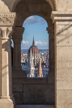 Red dome of Hungarian Parliament throuh corridor view on Fishermans Bastion on Buda hill in Budapest