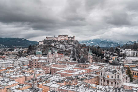 Aerial drone shot view of snowy Salzburg old town and Hohensalzburg fortress on the hill with heavy clouds in winter