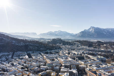 Aerial drone view of Salzburg snowy north town with view of Unesberg mountain in winter morning