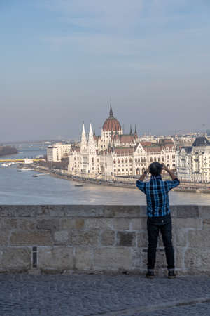 Tourist take photo of Parliament by danube river from Buda Castle hill