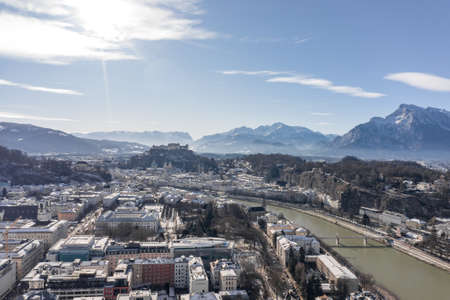 Aerial drone view of Salzburg snowy old town with view of Hohens Stockfoto