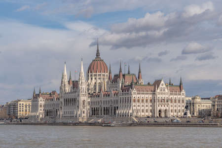 Hungarian Parliament facing Danube with clouds overhead in Budapest winter morning