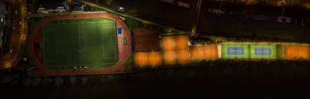 Aerial panoramic overhead shot of lights on tennis courts at night at Neuilly Tennis Association in Paris France