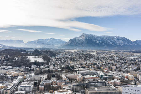 Aerial drone shot view of Salzburg aiglhof station with view of snowy alps mountain range in winter