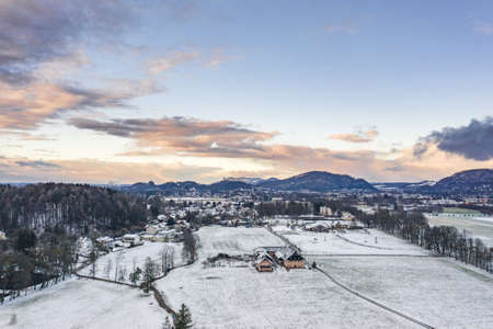 Aerial view of Austrian Alps valley village near Salzburg outskirts in winter during heavy snow time