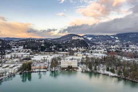 Aerial drone shot view of Leopoldskroner lake southwest of outskirts of Salzburg during winter