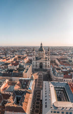 Aerial drone shot of St. Stephens Basilica with empty square in Budapest sunrise glow