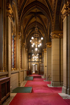 Budapest, Hungary - Feb 10, 2020: Rib vaults corridor with red carpet and gold ceiling lamp in Parliament Building