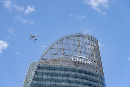 Paris, France - Jun 13, 2020: Plane fly over Tour T1 Engie skyscraper in La Defense
