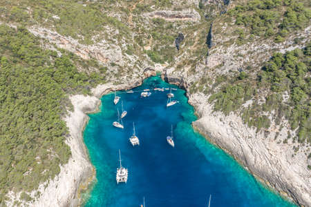 Aerial drone shot of yachts at Stiniva cove of blue Adriatic sea on Vis Island in Croatia summer Banque d'images