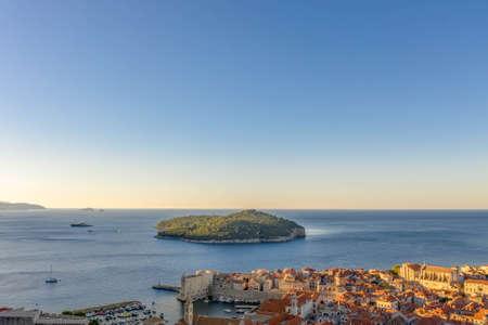 Aerial drone shot of Otok Lokrum in Dubrovnik in with port view in Croatia summer sunrise