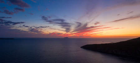 Aerial panorama drone shot of sunset burning sky clouds on Komiza town over Vis Island in Croatia Summer