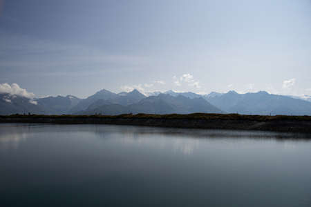 artificial lake with the Austrian Alps in the background