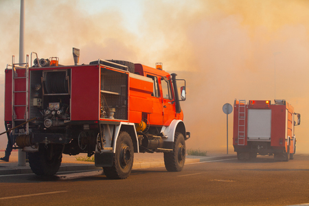 Two firefighter trucks in the middle of a smoke cloud  Stock Photo - 23439960