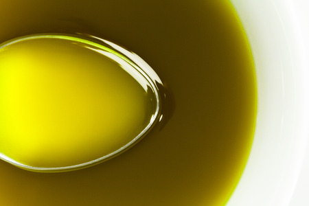 Close up Spoon under extra virgin olive oil. Stock Photo