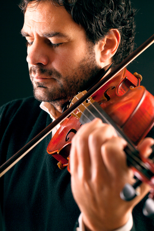 Musician playing violin in black background. 스톡 사진