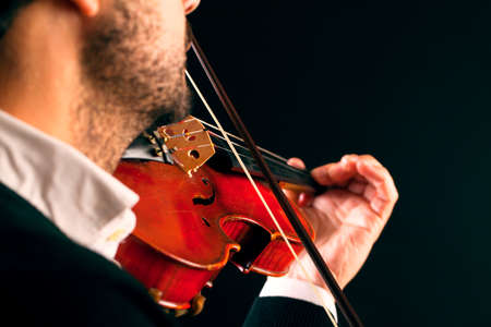 Musician playing violin in black background, macro. Soft focus. Stock Photo