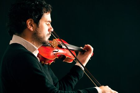 Musician playing violin in black background. Stock Photo
