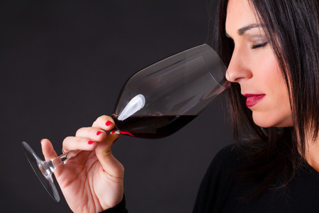 Woman smelling a wine, during wine marriage process. Standard-Bild