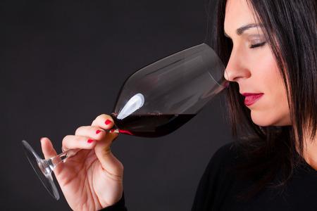 olfato: Mujer que huele un vino, durante el proceso del matrimonio vino. Foto de archivo