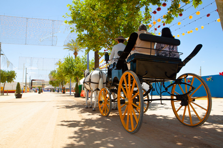 flemish: People in a horse carriage at the fair in Spain.