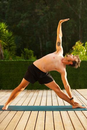 Man doing yoga outside. Stock Photo