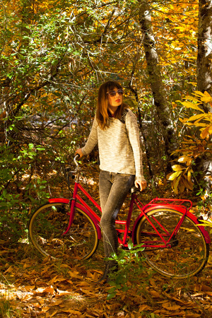 Woman with a bike in the middle of the forest.