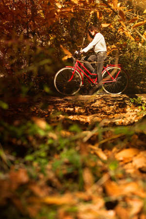 Woman with a bike in the middle of the forest 스톡 사진
