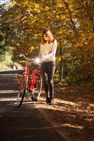 Woman posing with a bike near to the forest 스톡 사진