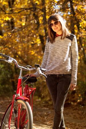 Woman posing with a bike near to the forest Stock Photo