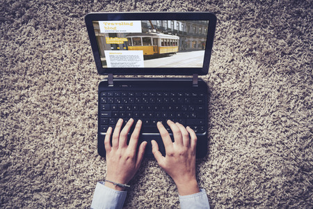 Hands typing on a laptop. Traveling blog on the screen. 스톡 사진