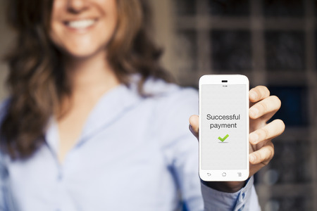 Secure payment on the screen. Smiling woman showing her mobile phone. Stock Photo