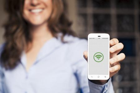 여자가 그녀의 휴대 전화를 게재 웃 고. 화면에 와이파이 아이콘입니다.