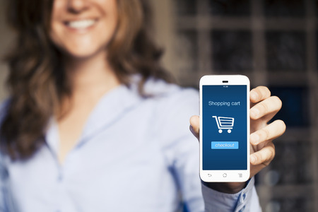 selling: Shopping cart on the screen. Smiling woman showing her mobile phone. Stock Photo