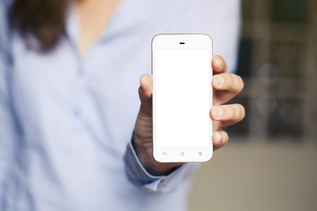 Woman showing mobile phone. White screen. Standard-Bild
