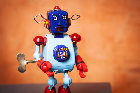 tin robot: Vintage tin robot in orange background.
