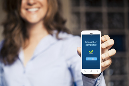 Smiling woman showing her mobile phone. Transaction completed text on the screen.