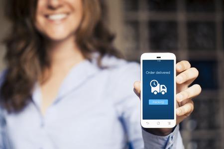 Mujer sonriente que muestra su teléfono móvil. Ordene mensaje de entrega en la pantalla. Foto de archivo - 43250792