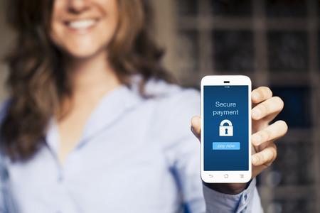 contrase�a: Mujer sonriente que muestra su tel�fono m�vil. Secure mensaje de pago en la pantalla.