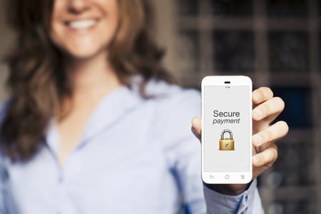 笑顔の女性は、彼女の携帯電話を示します。画面上のメッセージをセキュリティで保護されたお支払い。 写真素材