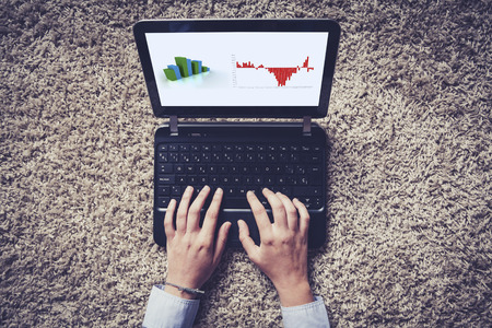 using a computer: Hands typing on a laptop.