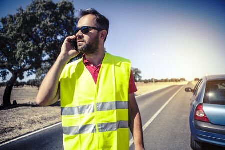 security vest: Man talking by phone after car failure. Stock Photo