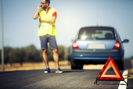 emergency vest: Car breakdown scene. Emergency triangle, stopped car and a man with a reflective vest talking by phone.