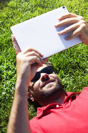 reading news: Man reading news in a tablet while lying on the grass. Stock Photo