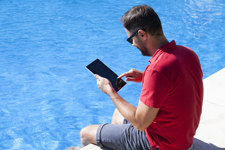 Man using a tablet. He is touching the screen while sitting at the poolside.