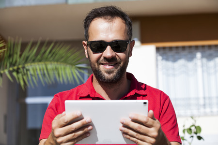 Man holding a tablet. Close up portrait.